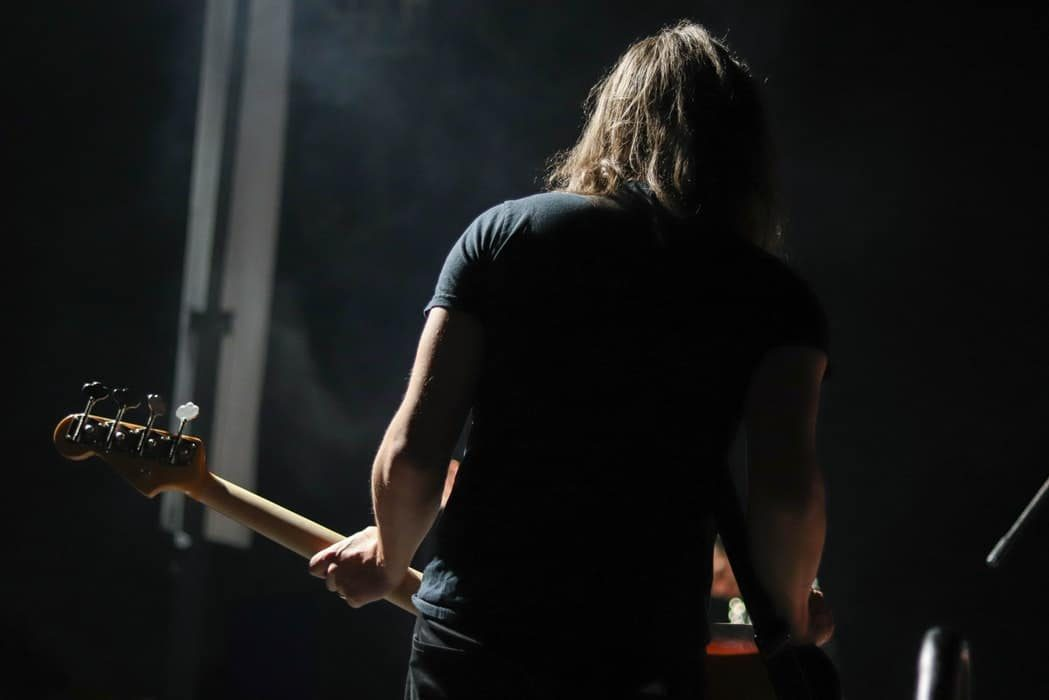 man with long hair with guitar back view
